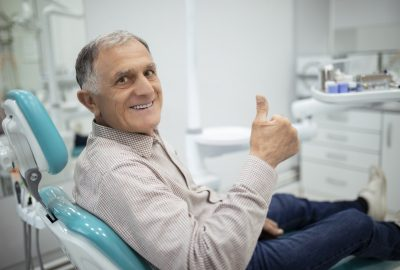Old senior man sitting in a dental chair thumb up
